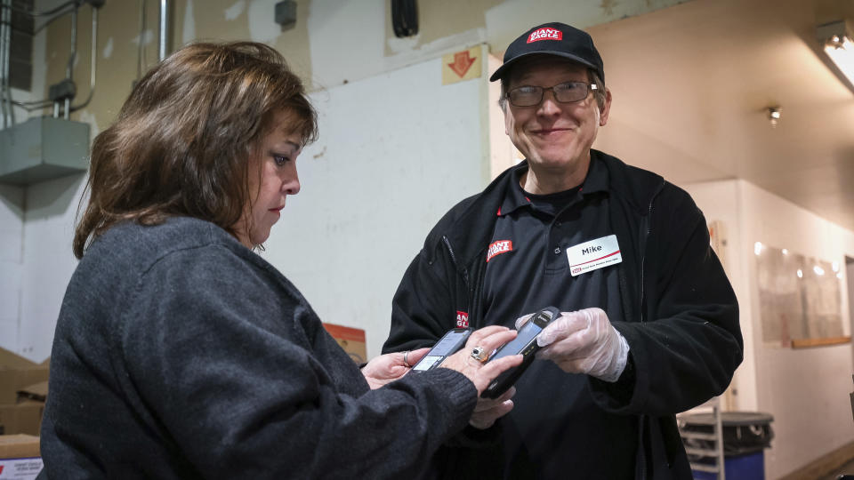 This Oct. 20, 2019 photo released by 412 Food Rescue shows a volunteer using the Food Rescue Hero app to check in at a Pittsburgh grocery store to pick up donated food. While millions of people struggle with food insecurity and hunger nationwide, the USDA estimates that more than 30% of the food in America is wasted each year. (Monica Godfrey-Garrison/412 Food Rescue via AP)