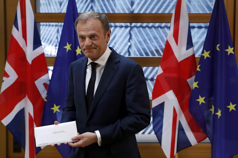 Sad day: Donald Tuck holds Theresa May's letter formally quitting the bloc: Yves Herman/Reuters