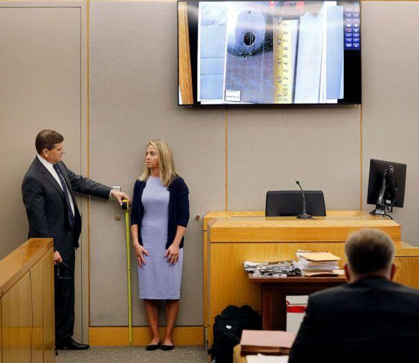 PHOTO: Defense attorney Toby Shook measures the height of a keyhole as fired Dallas police officer Amber Guyger stand against the courtroom wall as she testifies in her murder trial, Sept. 27, 2019, in Dallas. (Tom Fox/The Dallas Morning News via AP)