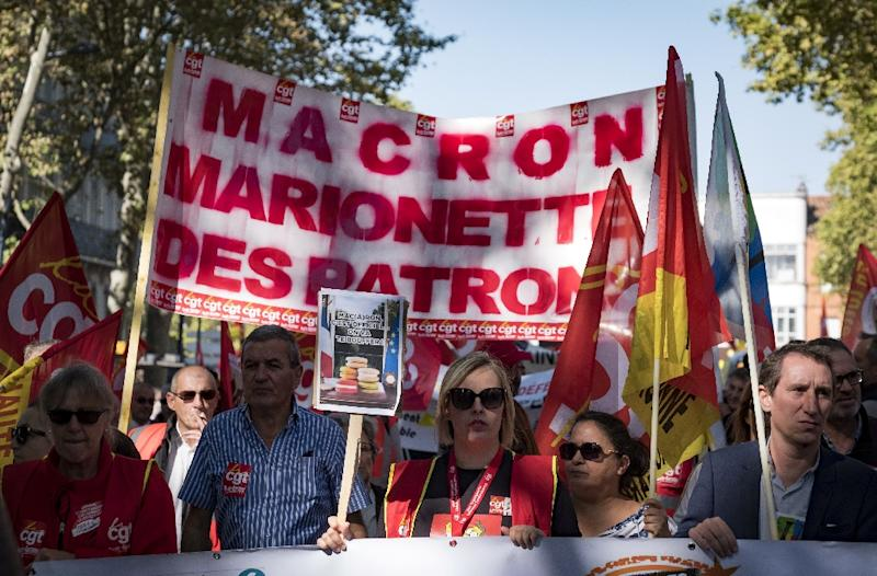 """People march with placards, flags and banners in Toulouse. The banner reads: """"Macron, puppet of the employers"""" (AFP Photo/ERIC CABANIS)"""