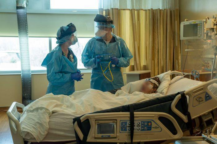 Two health workers in full PPE stand over a hospital bed with a woman lying in it