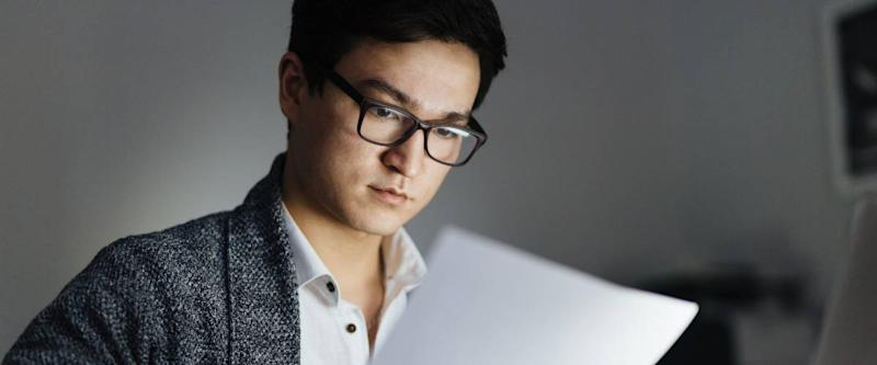 Asian man wearing glasses and casual wear reviewing credit report and working with laptop in dark room late at night, his face lit up by screen