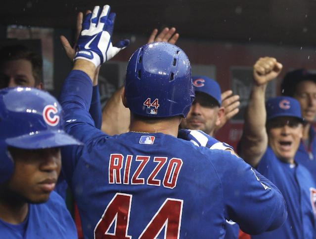 Chicago Cubs' Anthony Rizzo (44) is congratulated in the dugout after hitting a solo home run off Cincinnati Reds starting pitcher Johnny Cueto in the first inning of a baseball game, Tuesday, Aug. 26, 2014, in Cincinnati. (AP Photo/Al Behrman)