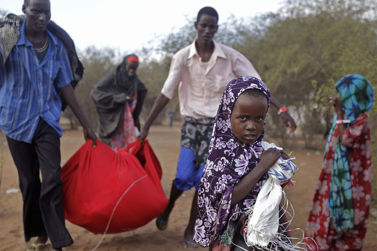 Men carry food stuff, left back, after they were handed food at a World Food Programme, WFP, compound in a displacement camp in Dadaab, Kenya, Sunday, July 31, 2011. Dadaab, a camp designed for 90,000 people now houses around 440,000 refugees. Almost all are from war-ravaged Somalia. Some have been here for more than 20 years, when the country first collapsed into anarchy. But now more than 1,000 are arriving daily, fleeing fighting or hunger.(AP Photo/Schalk van Zuydam)