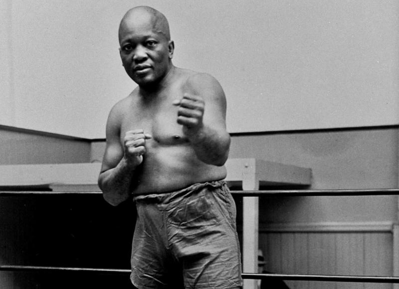 FILE - In this 1932 file photo, boxer Jack Johnson, the first black world heavyweight champion, poses in New York City. A Texas Gulf Coast home where Johnson once lived has been heavily damaged in a fire. The blaze caused a wall to collapse in the vacant home Friday, April 5, 2019 in Galveston, Texas. Fire Chief Mike Wisko said that the building was in the process of being renovated. (AP Photo/File)