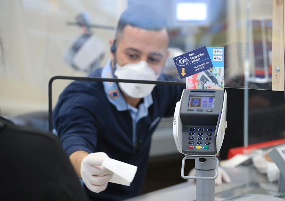 A cashier of the food discounter ALDI serves a customer, as the spread of the coronavirus disease (COVID-19) continues in Duesseldorf, Germany, April 29, 2020. REUTERS/Wolfgang Rattay