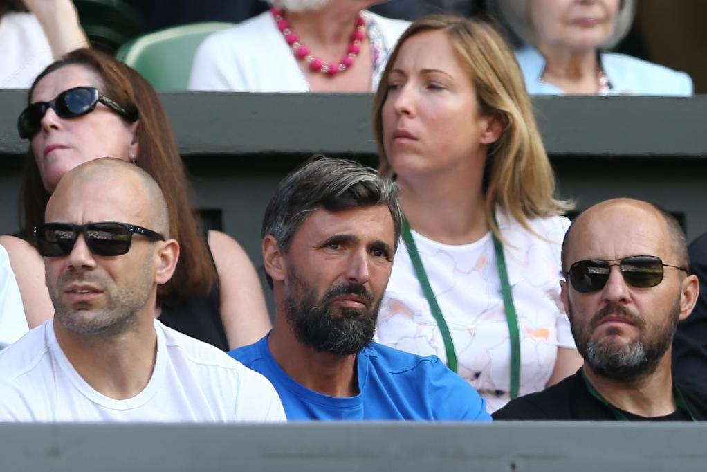 Croatian former tennis champion and tennis coach Goran Ivanisevic (C) sits watching Croatia's Marin Cilic play against Switzerland's Roger Federer during their men's singles quarter-final match on the tenth day of the 2016 Wimbledon Championships at The All England Lawn Tennis Club in Wimbledon, southwest London, on July 6, 2016. (AFP Photo/JUSTIN TALLIS)
