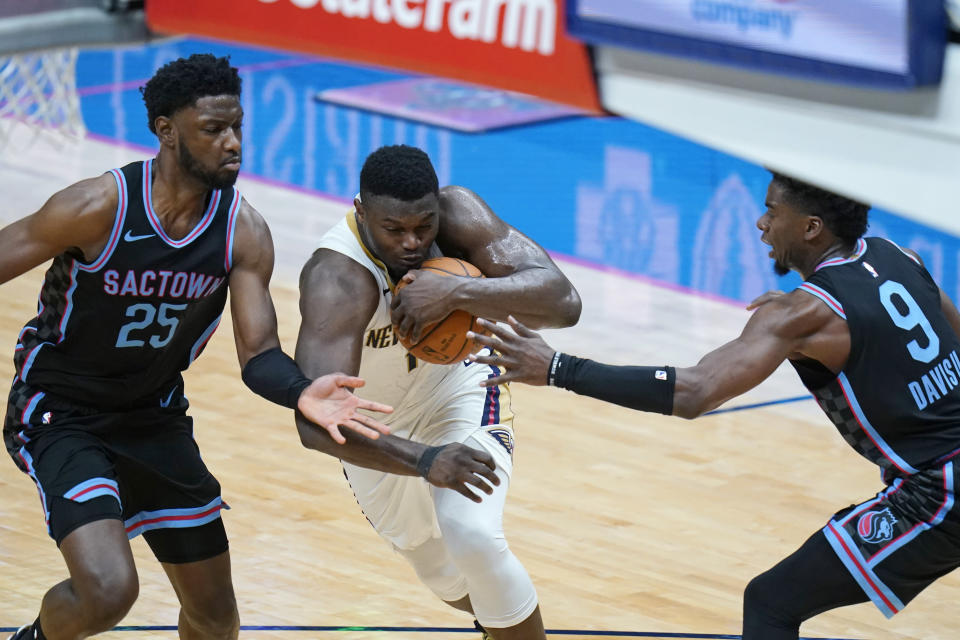 New Orleans Pelicans forward Zion Williamson drives to the basket between Sacramento Kings forward Chimezie Metu (25) and forward Terence Davis (9) in the second half of an NBA basketball game in New Orleans, Monday, April 12, 2021. (AP Photo/Gerald Herbert)