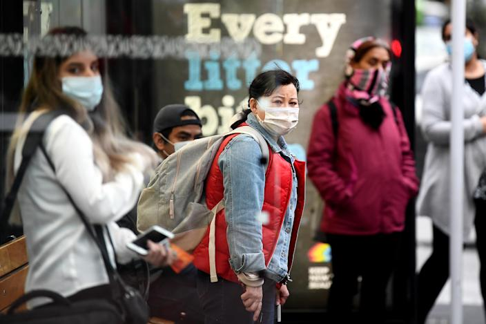 AUCKLAND, NEW ZEALAND - AUGUST 31: Members of the public wearing face masks wait for a bus on August 31, 2020 in Auckland, New Zealand. Face coverings are now compulsory for all New Zealanders over the age of 12 on public transport or planes under current Alert Level restrictions in place across the country. Auckland is currently at Alert Level 2.5 while the rest of New Zealand is at Alert Level 2. (Photo by Hannah Peters/Getty Images)