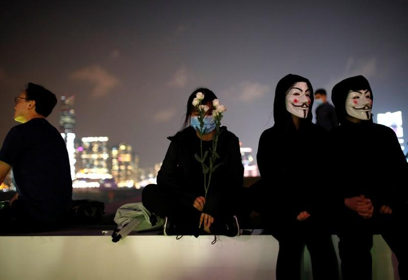 A woman holds flowers at Tamar Park, outside the Legislative Council (Legco) building, during a prayer and remembrance ceremony in Hong Kong