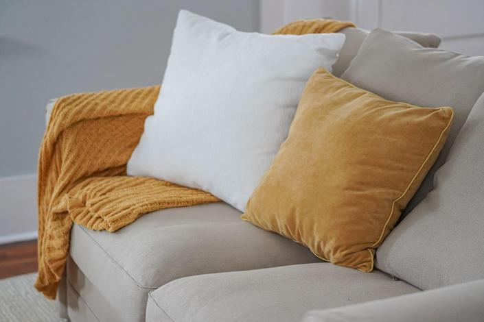 """<p>The method used for <a href=""""https://www.livingspaces.com/inspiration/ideas-advice/how-tos/how-to-clean-throw-pillows"""" rel=""""nofollow noopener"""" target=""""_blank"""" data-ylk=""""slk:cleaning throw pillows and blankets"""" class=""""link rapid-noclick-resp"""">cleaning throw pillows and blankets</a> depends on their material, so be sure to check out the manufacturer's care label to find washing instructions. According to Living Spaces, silks and velvets typically require the use of dry cleaning fluid, while other materials, like cotton or polyester, can usually handle gentle washing with water. To wash pillows and blankets, machine wash in warm water on the delicate cycle and let hang dry. Be sure to wash pillow covers separately from the cushion. </p><p>To sponge clean pillows, use a sponge and upholstery shampoo to scrub the pillow in circles, and then blot the excess moisture and shampoo with clean white towels. If dry cleaning is indicated, use a sponge dipped into dry cleaning solution to clean the fabric using the same circular motion and then blot dry. </p>"""