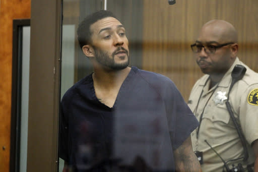 Former NFL football player Kellen Winslow Jr., center, looks through protective glass during his arraignment Friday, June 15, 2018, in Vista, Calif. The former tight end was arrested Thursday on charges of rape and other sex crimes, the day he was to appear in court on an unrelated burglary charge. (Hayne Palmour/San Diego Union-Tribune via AP, Pool)
