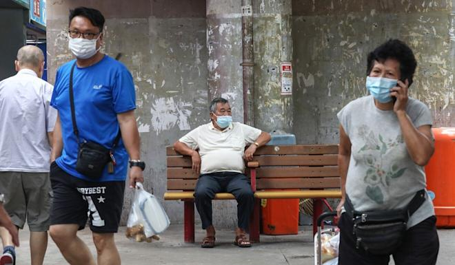 An elderly man in a face mask sits alone on a bench in Lam Tin. Photo: Jonathan Wong