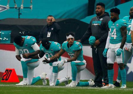 Miami Dolphins players kneel during the U.S. national anthem before the match Action Images via Reuters/Paul Childs