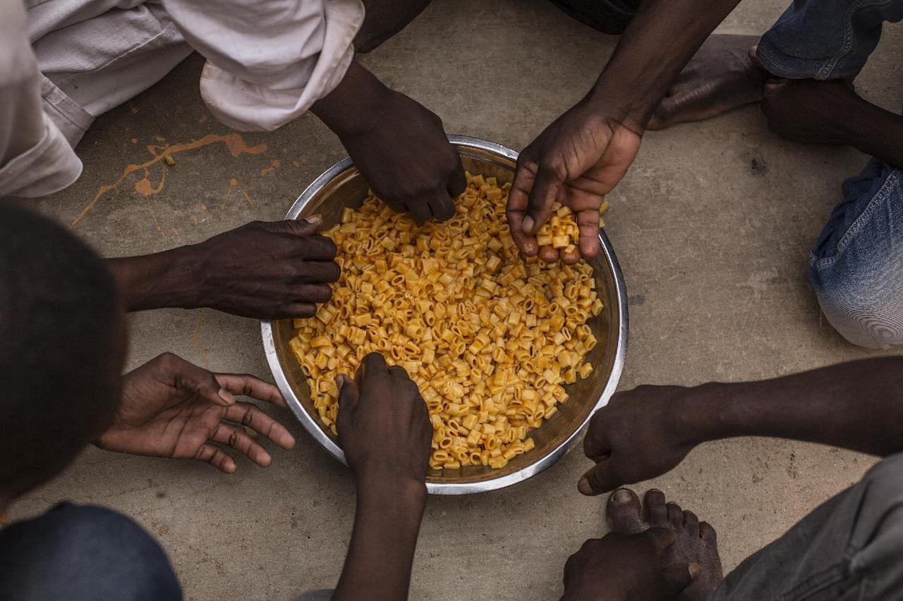 Migrants share a bowl of pasta during their lunch at the courtyard of a detention center for migrants, in the village of Karareem, around 50 km from Misrata, Libya, Sunday, Sept. 25, 2016. Libya is an important transit and destination country for migrants who arrive seeking employment or a path to Europe. Some 700,000 to 1 million migrants are estimated to be in the country, according to International Organization for Migration. (AP Photo/Manu Brabo)