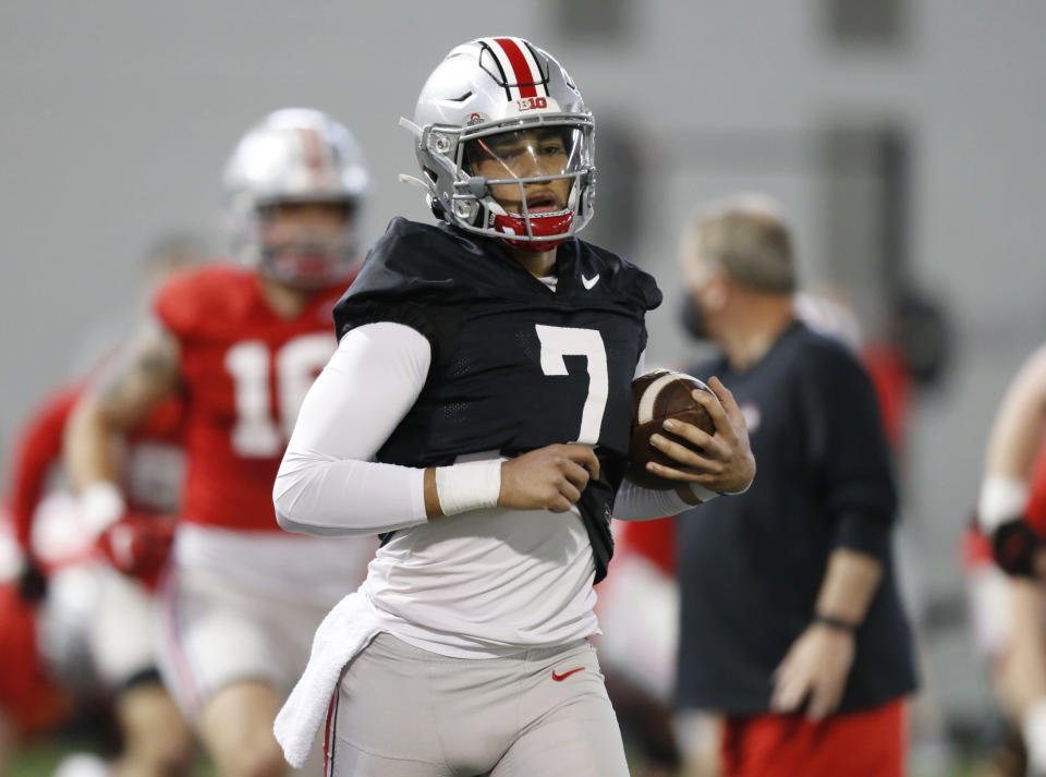 FILE - In this April 5, 2021 file photo, Ohio State quarterback C.J. Stroud runs through a drill during an NCAA college football practice in Columbus, Ohio. Ohio State is one of several national title contenders turning to a new quarterback this season, and C.J. Stroud takes over for the Buckeyes without a single college pass attempt. His debut for the four-time defending Big Ten champions comes on Thursday, Sept. 2 on the road against an experienced Minnesota team. (AP Photo/Paul Vernon, File)
