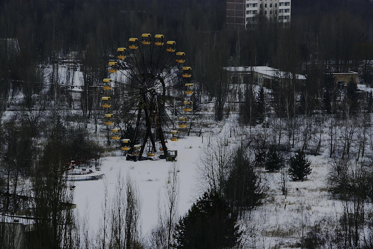 CHERNOBYL - JANUARY 25:  An abandoned ferris wheel is seen in a childrens fairground in the town of Pripyat on January 25, 2006 near Chernobyl, Ukraine. The town of Pripyat, deserted since the 1986 catastrophe, once housed 30,000 people, the majority of being workers from the Chernobyl Nuclear Power Plant. Days after the catastrophe the inhabitants were relocated to other locations in the Soviet Union. The town of Pripyat has remained uninhabited since the Catastrophe. Prypyat and the surrounding area will not be safe for human habitation for several centuries. Scientists estimate that the most dangerous radioactive elements will take up to 900 years to decay sufficiently to render the area safe. (Photo by Daniel Berehulak/Getty Images)