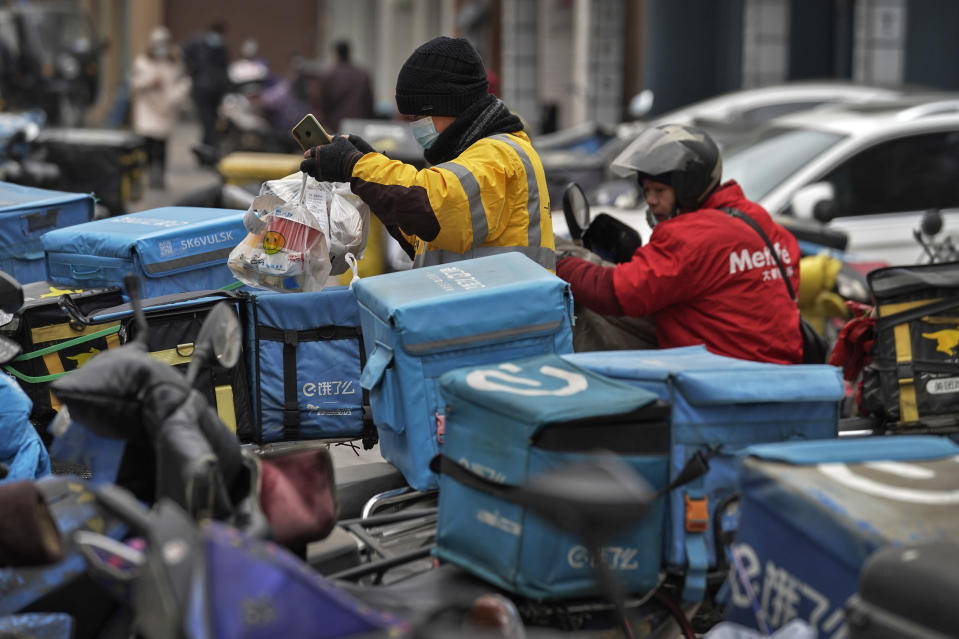 A food delivery worker wearing a face mask to help curb the spread of the coronavirus prepares to deliver foods for his customers outside a restaurant in Beijing on Thursday, Jan. 14, 2021. The e-commerce workers and delivery people who kept China fed during the pandemic, making their billionaire bosses even richer, are so unhappy with their pay and treatment that one just set himself on fire in protest. (AP Photo/Andy Wong)