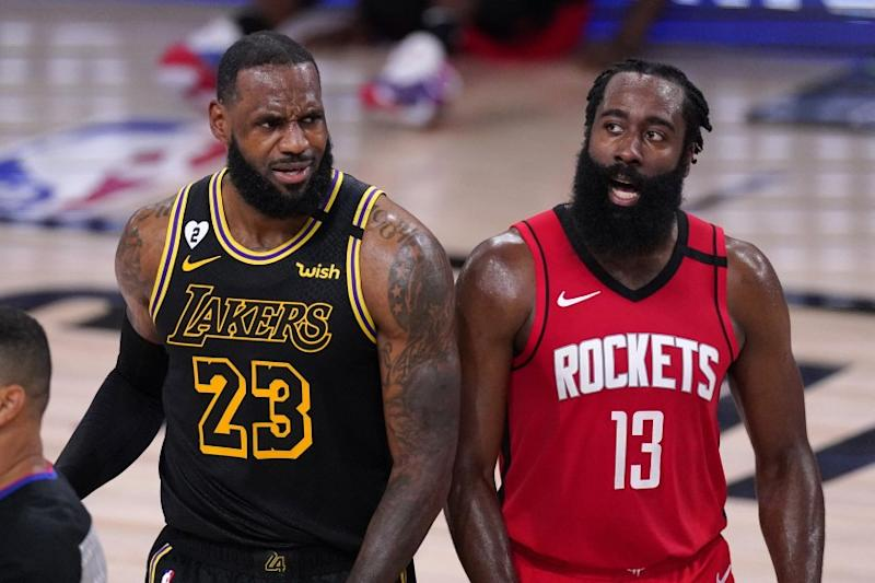 Los Angeles Lakers' LeBron James (23) and Houston Rockets' James Harden (13) react to a call.