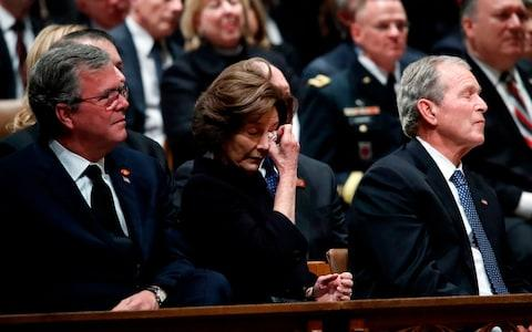 Laura Bush wipes away a tear as her husband concludes his eulogy - Credit: AFP