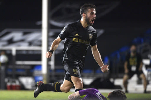 Los Angeles FC forward Diego Rossi celebrates after scoring a goal past LA Galaxy goalkeeper David Bingham, below, during the second half of an MLS soccer match, early Sunday, July 19, 2020, in Kissimmee, Fla. (AP Photo/Phelan M. Ebenhack)