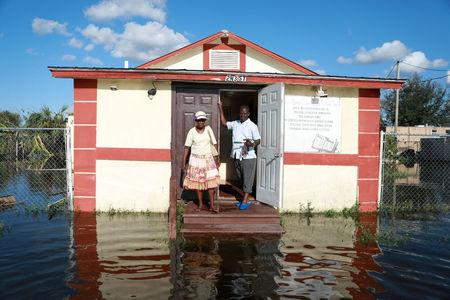 Pastor Louicesse Dorsaint stands with his wife Maria Dorsaint in front of their church, Haitian United Evangelical Mission, which was damaged by flooding from Hurricane Irma in Immokalee