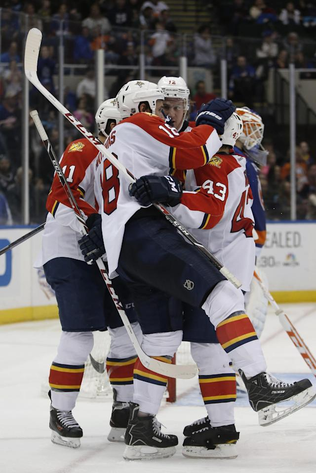 Florida Panthers players celebrate with center Shawn Matthias (18) in the third period of an NHL hockey game at Nassau Coliseum in Uniondale, N.Y., Sunday, March 2, 2014. Matthias had two goals, one in the second and one in the third, as the Panthers defeated the Islanders 5-3. (AP Photo/Kathy Willens)