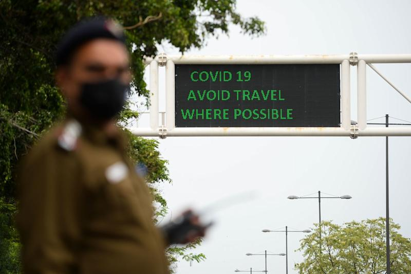 A policeman wearing a mask stands along a road in New Delhi, India.