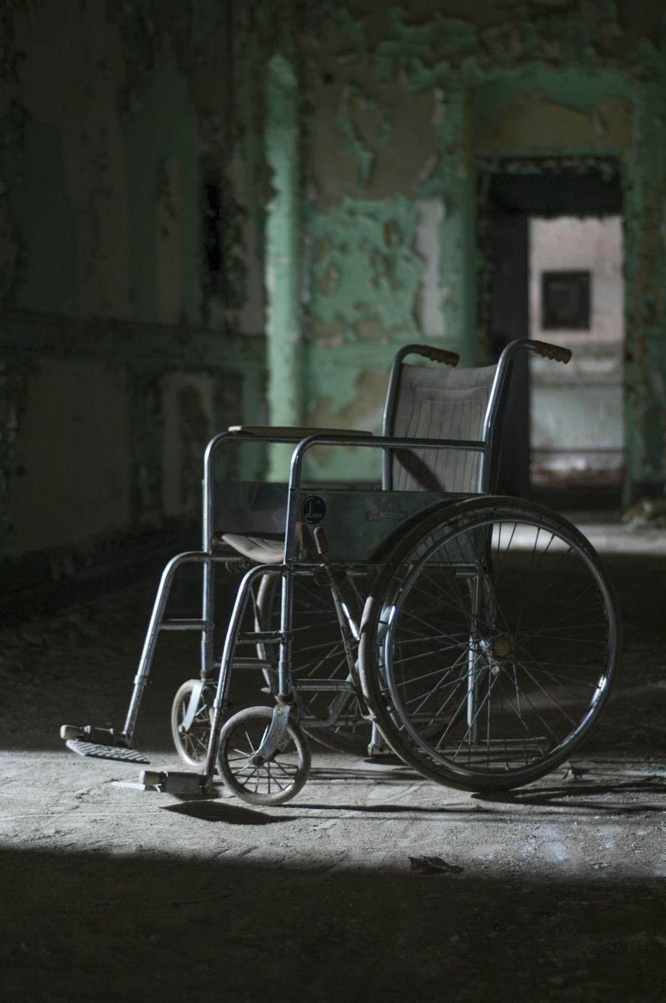 <p>A lone wheelchair sits in the middle of the hallway in an abandoned mental asylum. </p>