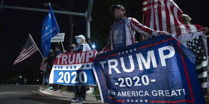 People carry Trump flags and U.S. flags at a street corner.