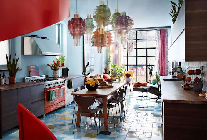 """In the open kitchen and dining area, the table and cabinetry are by <a href=""""https://www.ikea.com/us/en/"""" rel=""""nofollow noopener"""" target=""""_blank"""" data-ylk=""""slk:Ikea"""" class=""""link rapid-noclick-resp"""">Ikea</a> and the range is by <a href=""""https://us.bertazzoni.com/"""" rel=""""nofollow noopener"""" target=""""_blank"""" data-ylk=""""slk:Bertazzoni"""" class=""""link rapid-noclick-resp"""">Bertazzoni</a>; the rear window wall looks out onto a courtyard created in collaboration with liz Campbell Kelly of <a href=""""http://www.hudsongardenstudio.com/"""" rel=""""nofollow noopener"""" target=""""_blank"""" data-ylk=""""slk:Hudson Garden Studio."""" class=""""link rapid-noclick-resp"""">Hudson Garden Studio.</a>"""