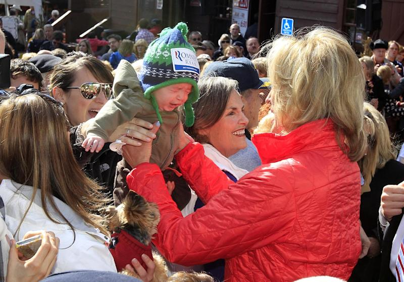 Ann Romney, wife of Republican presidential candidate, former Massachusetts Gov. Mitt Romney is handed a baby from the crowd after addressing supporters at the Franklin Cider Mill in Bloomfield Hills, Mich., Friday, Oct. 12, 2012. (AP Photo/Carlos Osorio)