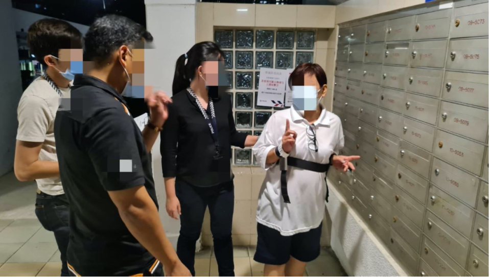 A female suspect escorted to crime scene to identify letterboxes which she stole Budget 2020 Grocery Vouchers from. (PHOTO: Singapore Police Force)
