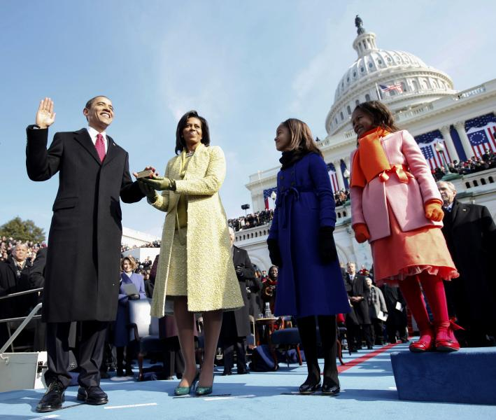 FILE - In this Jan. 20, 2009, file photo, Barack Obama, left, takes the oath of office from Chief Justice John Roberts, not seen, as his wife Michelle, holds the Lincoln Bible and daughters Sasha, right and Malia, watch at the U.S. Capitol in Washington. Obama's second inauguration is shaping up as a high-energy celebration smaller than his first milestone swearing-in, yet still designed to mark his unprecedented role in American history with plenty of eye-catching glamour. A long list of celebrity performers will give the once-every-four years right of democratic passage the air of a star-studded concert, from the bunting-draped Capitol's west front of the Capitol, where Obama takes the oath Jan. 21, to the Washington Convention Center, which is expected to be packed with 40,000 ball-goers that evening. (AP Photo/Chuck Kennedy, Pool)