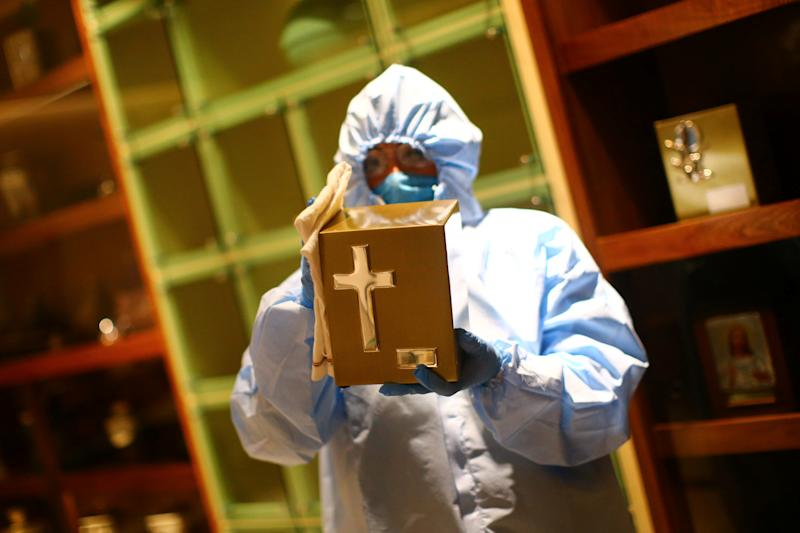 An employee wearing protective clothing disinfects a box for holding ashes at Funeral Gayosso, as the outbreak of the coronavirus disease (COVID-19) continues in Mexico City, Mexico May 11, 2020. Picture taken May 11, 2020. REUTERS/Edgard Garrido