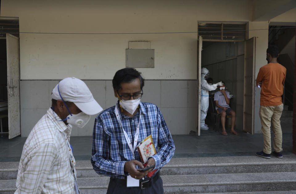 Officials talk as a health worker takes a nasal swab sample for COVID-19 at testing center in New Delhi, India, Saturday, Oct. 3, 2020. India has crossed 100,000 confirmed COVID-19 deaths on Saturday, putting the country's toll at nearly 10% of the global fatalities and behind only the United States and Brazil. (AP Photo/Manish Swarup)