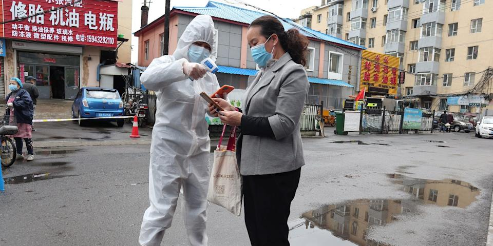 A worker in protective suit takes the body temperature measurement of a woman following an outbreak of coronavirus in Jilin, Jilin province, China May 17, 2020.