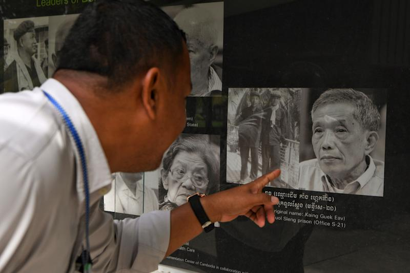 A man looks at a portrait of former head of the Tuol Sleng prison Kaing Guek Eav, also known as Duch, at the Tuol Sleng genocide museum in Phnom Penh on September 2, 2020. - Kaing Guek Eav, 77, better known by his alias Duch, the chief torturer behind Cambodias genocidal Khmer Rouge, died on September 2 while serving a life sentence for crimes against humanity, leaving just one surviving leader of the regime that killed an estimated two million people in the 1970s. (Photo by TANG CHHIN Sothy / AFP) (Photo by TANG CHHIN SOTHY/AFP via Getty Images) (Photo: TANG CHHIN SOTHY via Getty Images)