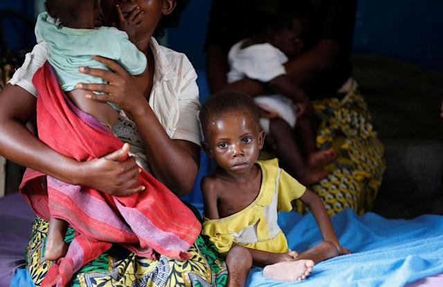 <p>An internally displaced woman sits with her severely acute malnourished children as they wait to receive medical attention at the Tshiamala general referral hospital of Mwene Ditu in Kasai Oriental Province in the Democratic Republic of Congo, March 15, 2018. (Photo: Thomas Mukoya/Reuters) </p>