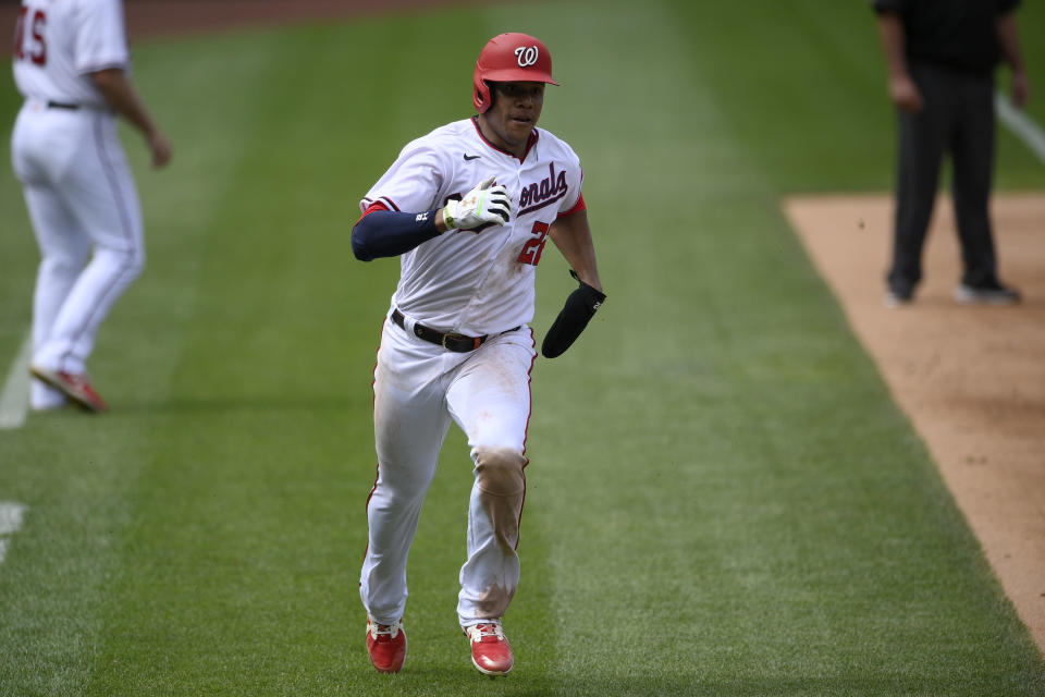 Washington Nationals' Juan Soto runs towards home to score on a double by Josh Harrison during the fourth inning of the first baseball game of a doubleheader against the San Francisco Giants, Saturday, June 12, 2021, in Washington. This game is a makeup of a postponed game from Thursday. (AP Photo/Nick Wass)