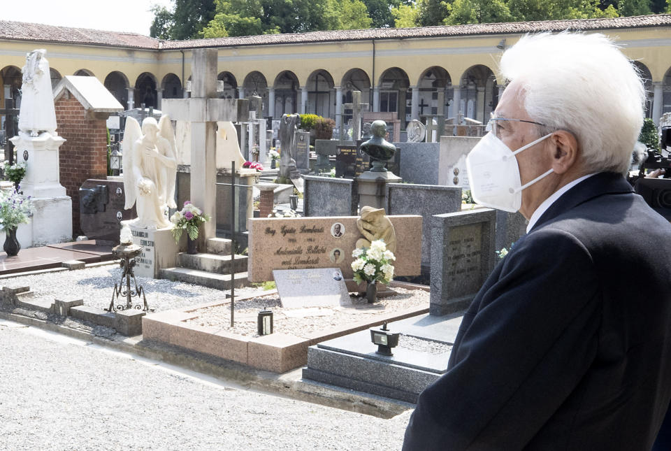 """FILE - In this Tuesday, June 2, 2020 file photo, Italian President Sergio Mattarella stands silent in front of graves, at the cemetery of Codogno, Italy, where the first case of COVID-19 emerged. Pope Francis and Italy's president have marked the nation's first annual day to honor doctors, nurses and other health care workers, exactly a year after the nation's first known native case of COVID-19 emerged. In a message to honor those caring for COVID-19 patients, Frances hailed the """"generous involvement, at times heroic, of the profession lived as mission."""" (Paolo Giandotti/Italian Presidency via AP)"""