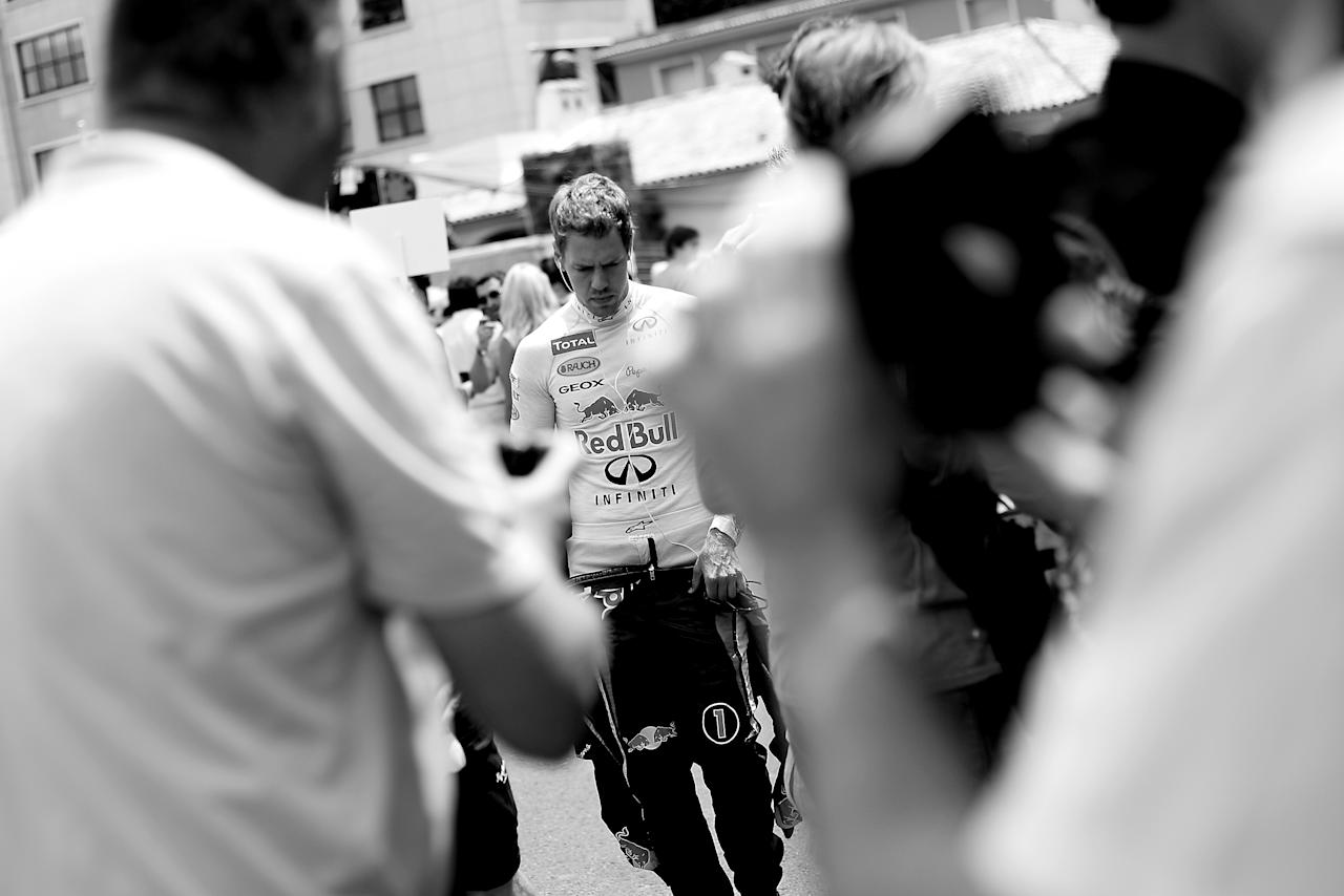 MONTE CARLO, MONACO - MAY 27: (EDITORS NOTE: THIS BLACK AND WHITE IMAGE WAS CONVERTED FROM AN ORIGINAL COLOUR FILE) Sebastian Vettel of Germany and Red Bull Racing walks towards his garage ahead of the Monaco Formula One Grand Prix at the Circuit de Monaco on May 27, 2012 in Monte Carlo, Monaco.  (Photo by Vladimir Rys Photography via Getty Images)