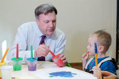 Ed Balls with a child in a nursery