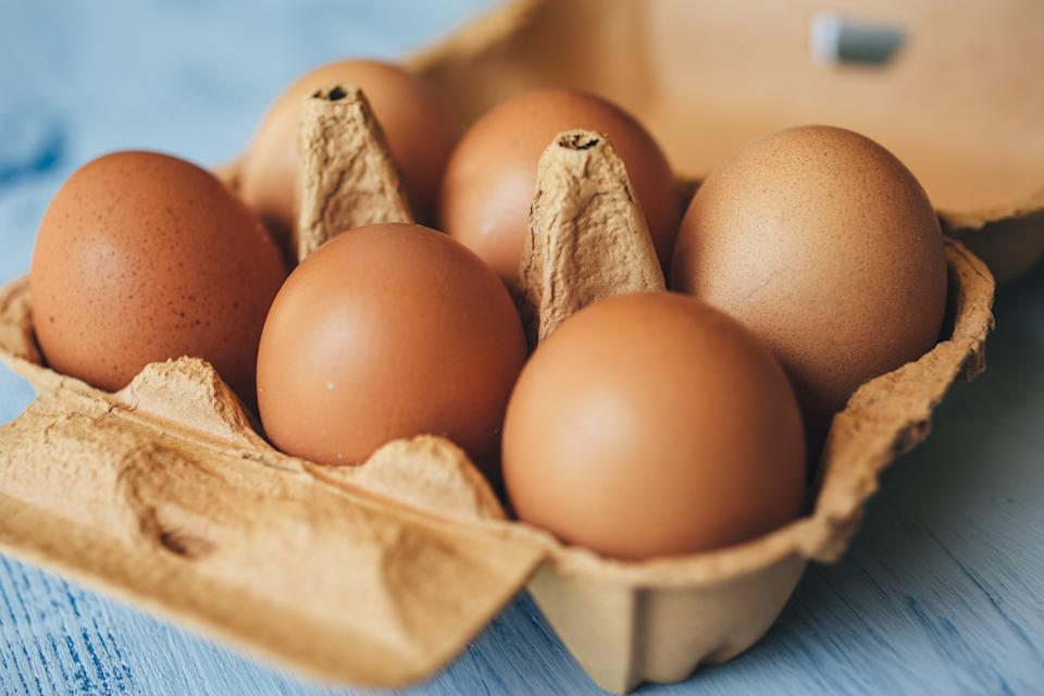 Closeup view of eggs in carton box on wooden table