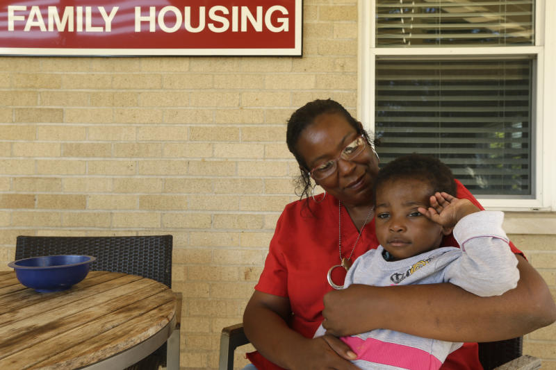 In this photo taken Thursday, Oct. 10, 2013, Nia Sockwell holds her granddaughter, Heaven, 1, outside a housing unit at Our House, a nonprofit organization that provides childcare, shelter and other programs for working homeless people in Little Rock, Ark. People have been donating to the organization to fill in the gaps left by missing federal money caused by the partial government shutdown. (AP Photo/Danny Johnston)