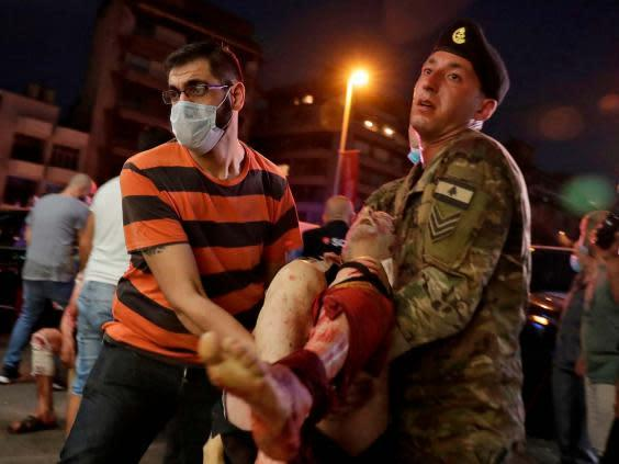 A Lebanese army soldier and a man carry away an injured man at a hospital in the aftermath of an explosion (AFP via Getty Images)