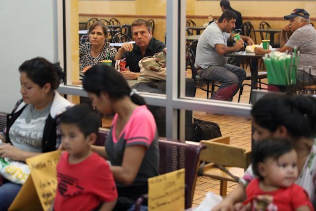 Diners inside a Subway restaurant look out at undocumented immigrant families just released from detention at a bus depot in McAllen, Texas, U.S., June 22, 2018. REUTERS/Loren Elliott TPX IMAGES OF THE DAY