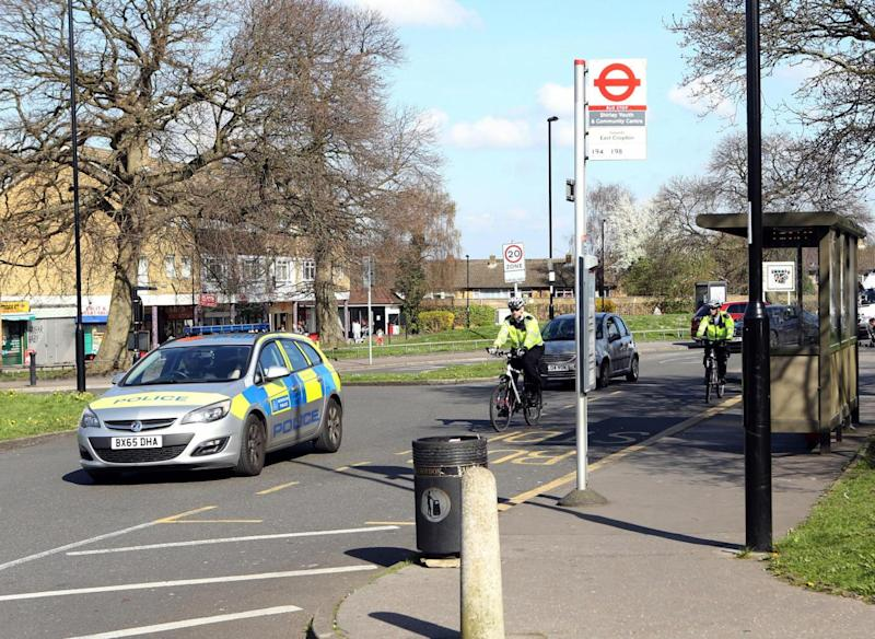 Police officers pass the bus stop in Croydon where a teenage asylum seeker was allegedly attacked (PA)