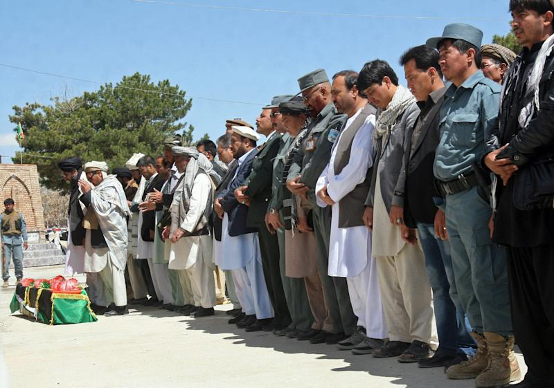 Afghan men offer funeral prayers near the body of deputy police chief Col. Mohammad Hussain, after the convoy he was traveling in was hit by a road side bomb in the district of Zana Khan, in Ghazni province west of Kabul, Afghanistan, Sunday, April 28, 2013. A remote-controlled roadside bomb killed three police officers in eastern Afghanistan on Sunday, an attack the Taliban claimed as the opening round of their spring offensive. U.S.-backed efforts to try to reconcile the Islamic militant movement with the Afghan government are gaining little traction. (AP Photo/Rahmatullah Nikzad)