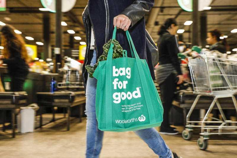 A woman carries a Woolworths reusuable bag through the supermarket.